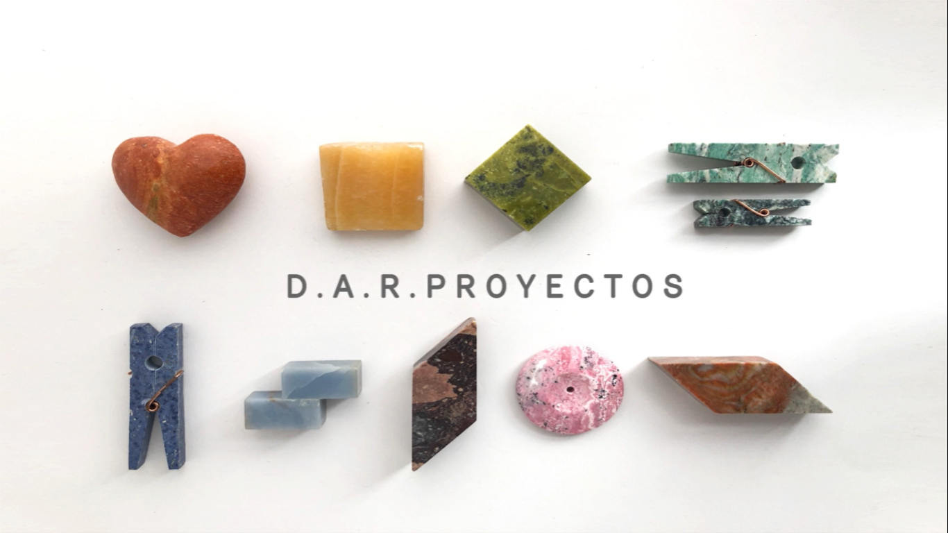 DAR PROYECTOS logo surrounded by coloured stones in geometric shapes.