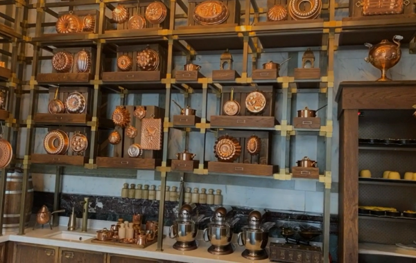 Room filled with wooden shelves lined with copper pots.